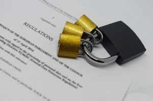 Closeup of padlocks laid out on document containing GDPR legislative text.